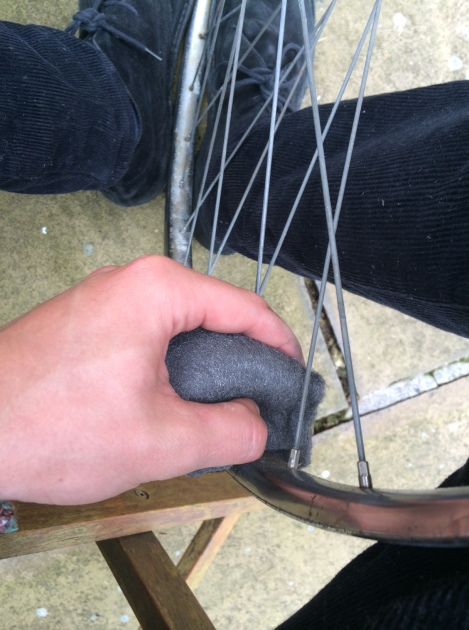 Back and forth rubbing with the steel wool in-between spokes working your way around the rim.